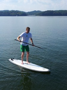 Standing unsteadily on a stand-up paddle board