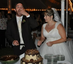 Alex chomps a piece of the grooms cake as Natalie looks on.