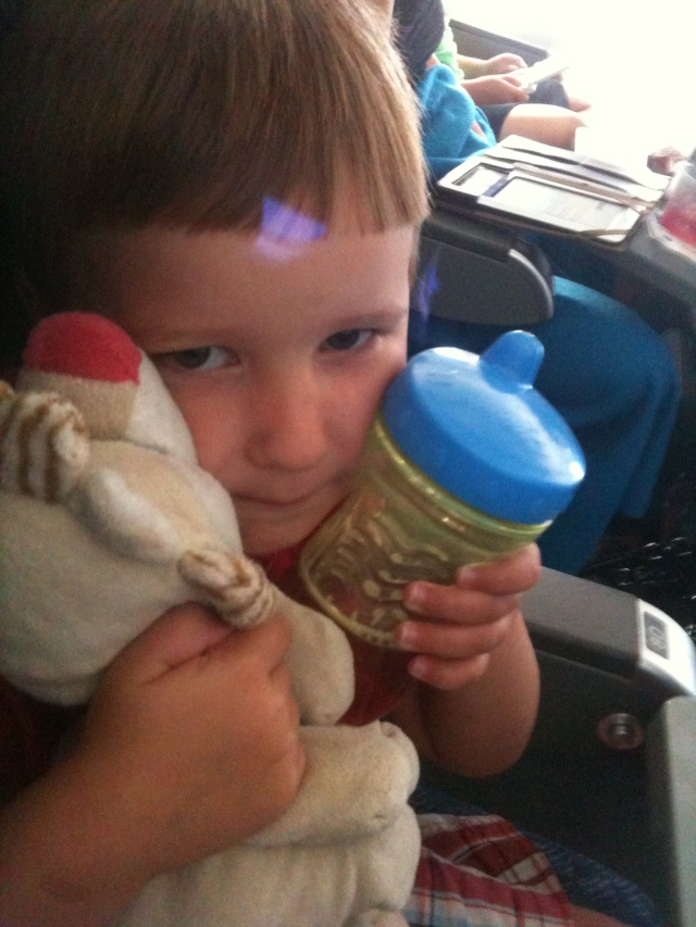 Carlton hangs on to Lion and his apple juice before his first plane ride back in June 2012.