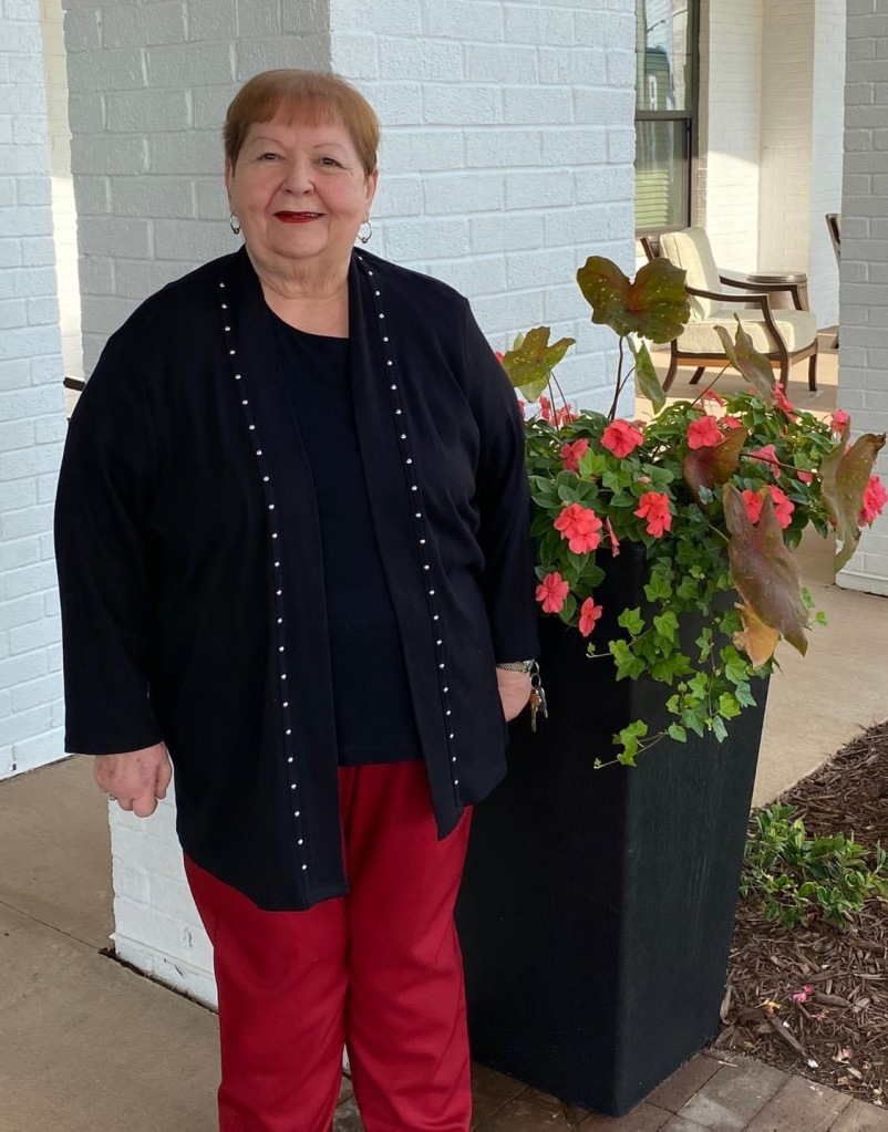 picture of Cynthia Barron standing beside a planter with coral-colored flowers