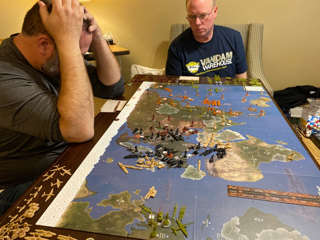 Lyle Wallace and Lee Wallace look at the Axis and Allies game board.
