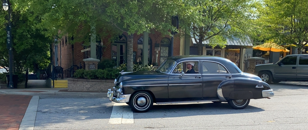 bearded young man in a cap drives a 1950 Chevrolet by brick buildings in downtown Lilburn