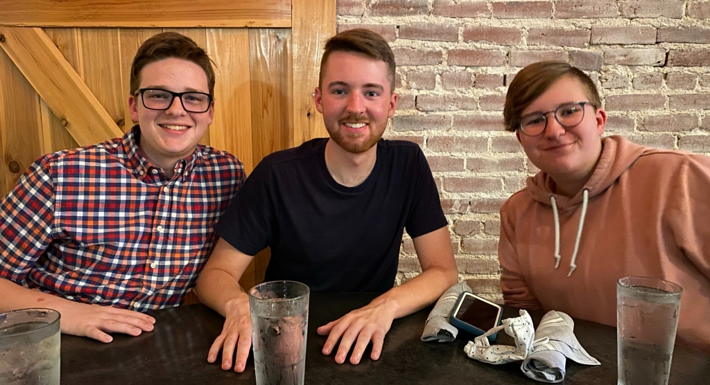 three young men pose for a portrait at a table in front of a brick and wood wall at 1910 Public House in Lilburn